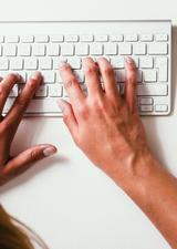 hands typing on a white keyboard