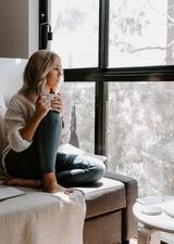 woman sitting on couch looking out a window