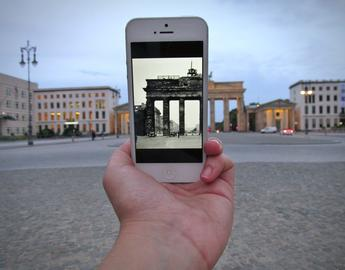 Image of student holding a picture on their phone of 1924 German architecture beside the same building in modern Berlin
