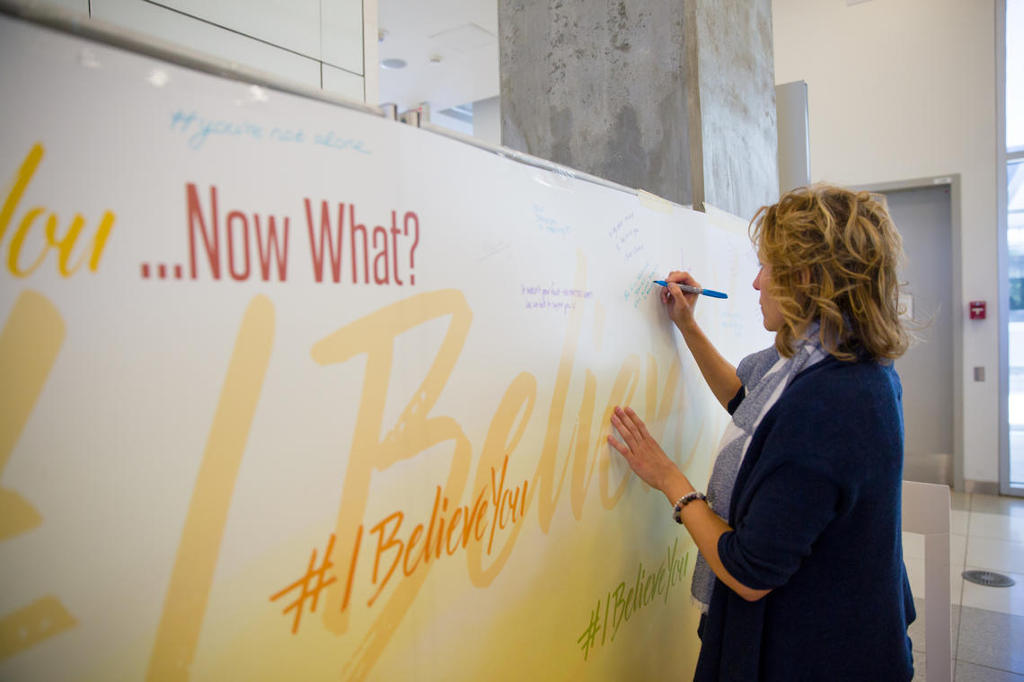 Sexual Violence Support Advocate Carla Bertsch adds her voice to the #IBelieveYou graffiti wall on campus. Photos by Riley Brant, University of Calgary