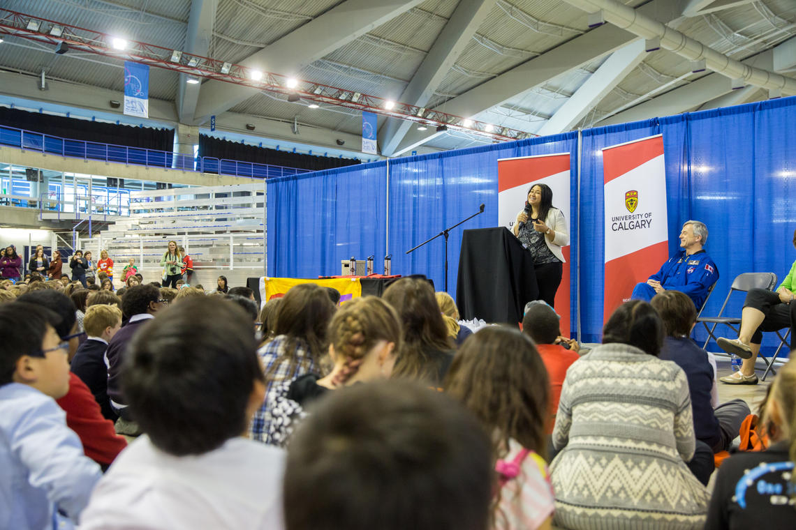 Amanda Black, a PhD student in the Faculty of Kinesiology, and University of Calgary Chancellor Robert Thirsk speak to students at the Calgary Youth Science Fair.