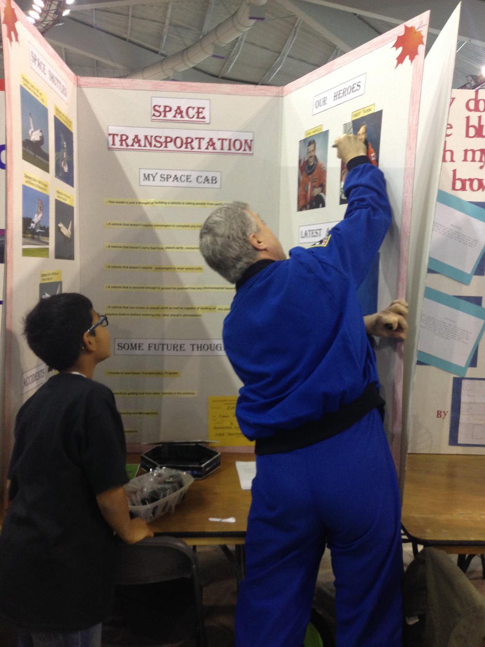 "Chancellor Thirsk writes a personal message to a young science fair participant, whose project was on space transportation. The young boy had a photo of Thirsk with the title ""Our Heroes"" on his project."