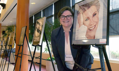 Annie Murray is head of Archives and Special Collections, which manages the EMI Music Canada Archive. She stands next to an image of Canadian singer Anne Murray on display at the announcement of the donation to the University of Calgary.