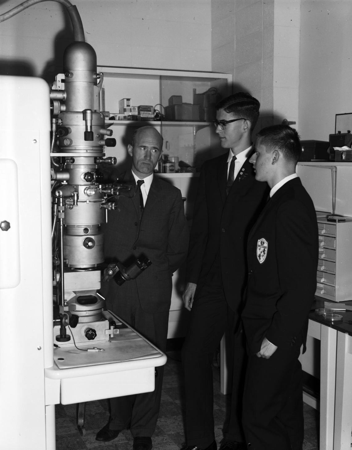 From left, Dr. Cyril E. Challice of the physics department with Canadian Association of Physicists prize winners James Prescott and Stephen Hernadi standing next to the university's electron microscope, 1960.