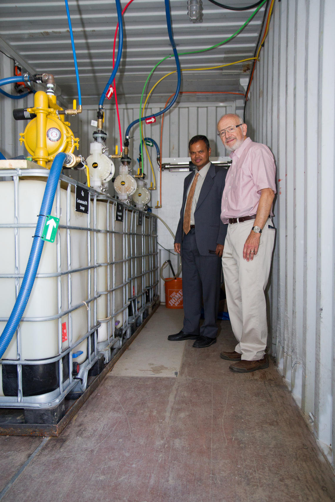 Gopal Achari, left, professor of civil engineering in the Schulich School of Engineering, and Cooper Langford, professor of chemistry in the Faculty of Science, stand inside the mobile PCB cleanup unit.