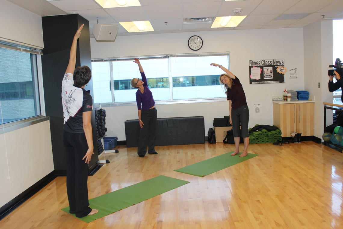 Linda Carlson, centre, and two breast cancer survivors demonstrate some of the yoga poses they did as part of the study.