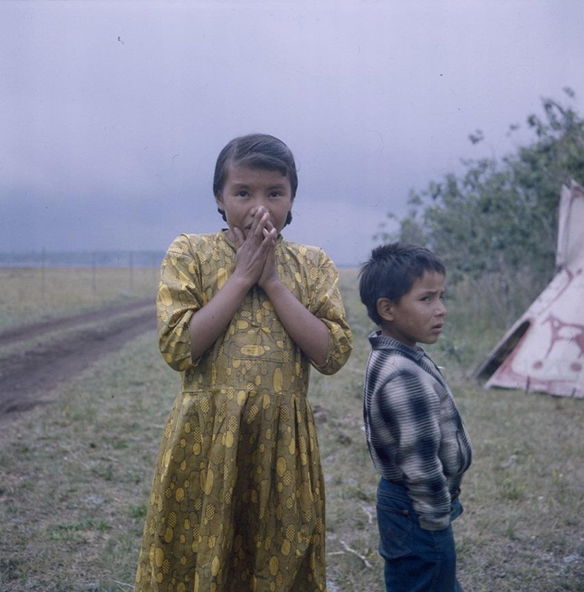 Two Indigenous children with teepee in background