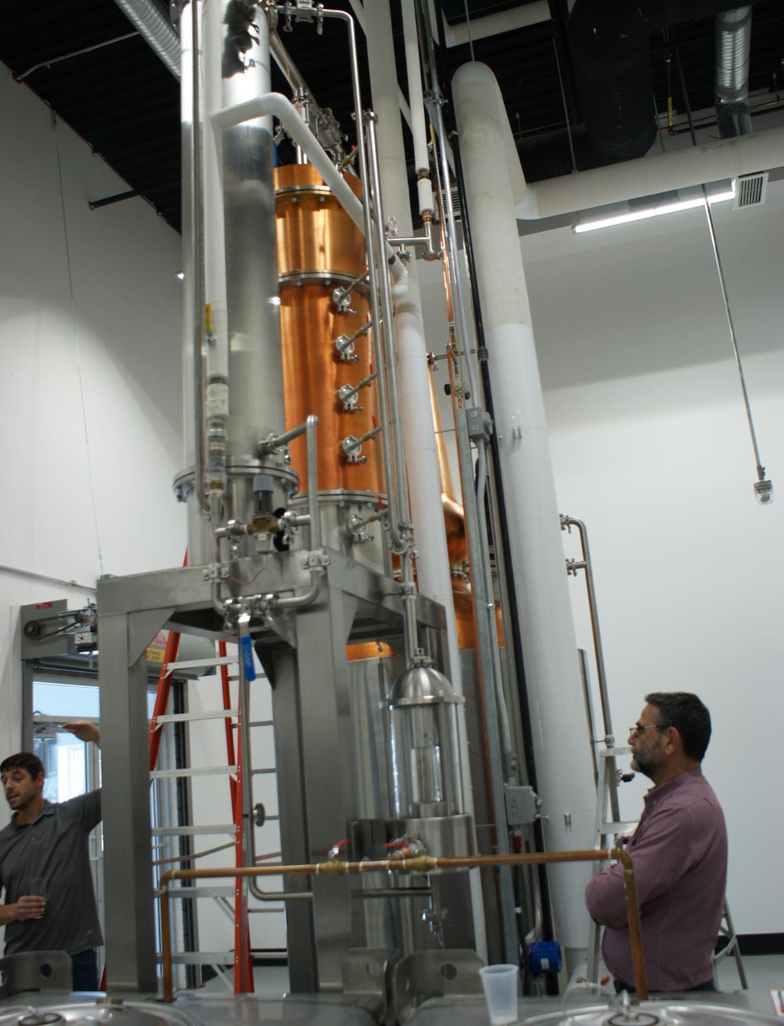 Tomas and Diego Romero in front of Romero Distilling Co.'s large pot stilling apparatus.