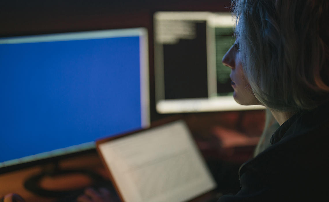 Woman sitting in a dark room with two monitors, one blue, one with coding, and a laptop