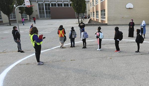 People wait in a physical distancing circle at the yard at Portage Trail Community School in Toronto on Sept. 15, 2020