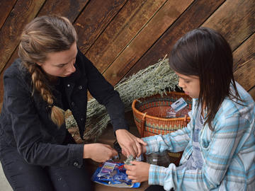 The AIM-HI Network led campers on a medicine walk in Fish Creek Park. Here, a camper is being shown how to make a sage bundle.
