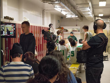 People gathered in a locker room with a film crew