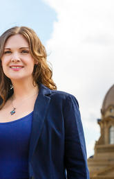 Alumna Jennifer Burgess stands in front of the Alberta legislature building
