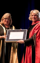 University of Calgary President Elizabeth Cannon, right, receives her honorary degree from Heather Culbert, chair of SAIT's Board of Governors.