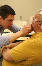 Scott MacKay performs an electroencephalography (EEG) recording on his father at the UCalgary Foothills campus.