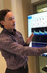 Aaron Phillips stands in front of a graph which shows how monitoring cerebral blood flow can test if enough blood is getting to the brain.