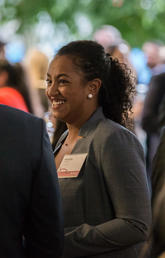 A Black female smiles in a crowd of people