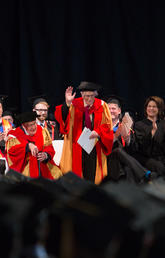 Dr. Richard Guy stands and waves as he is honoured at the 2016 UCalgary convocation ceremony for his 100th birthday.