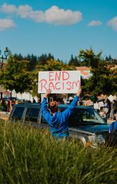 "A woman stands facing traffic holding a sign that says ""End Racism."""