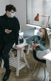 Two teenagers wearing face masks, one holding a cell phone